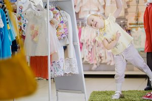 Little girl in a summer suit has fun in front of the mirror in the children's clothing store