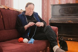 Elderly woman in glasses begins to knit