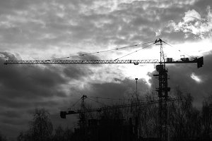 Construction cranes in front of sunset - black and white silhouette