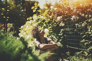 Black curly girl in summer garden