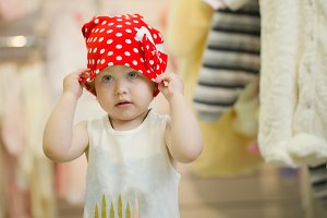 Little cute 3 years girl in a red hat polka dot at children clothes store