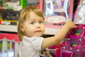 Happy little girl chooses toys in a children's store