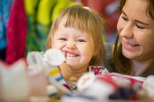 Mother and her little daughter have fun in children store