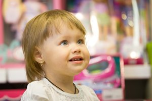 Portrait of the little girl among toys in children store