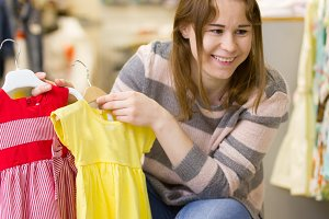 Mother shows dresses for her daughter - little girl in children clothes store