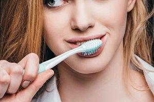 young woman brushing her teeth