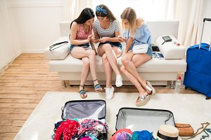 young women packing suitcases