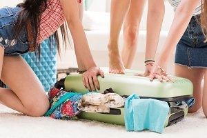 young women packing suitcase