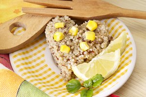 Quinoa salad with corn and lemon on yellow plate