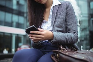 Businesswoman sitting near fountain and using mobile phone