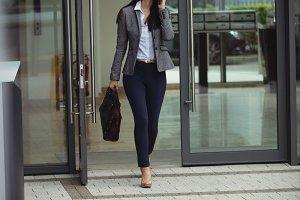 Businesswoman walking while talking on mobile phone