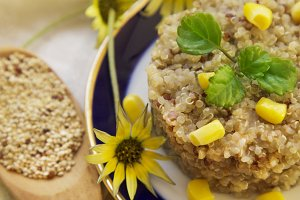 Wooden spoon with quinoa and yellow daisies
