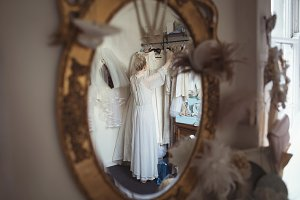 Reflection of bride selecting wedding dress from clothes hanger in the mirror