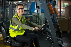 Bbeautiful female worker driving forklift in warehouse
