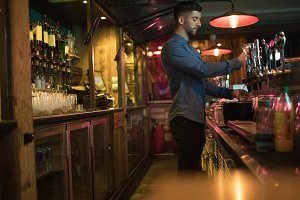 Bartender filling beer from bar pump