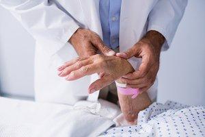 Doctor examining patients pulse