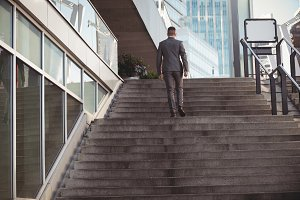 Businessman with a diary climbs up stairs