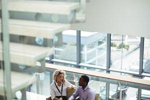 Business executives interacting in corridor