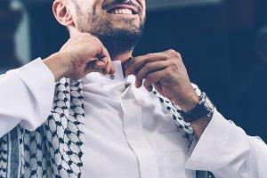 Cheerful man adjusting collar