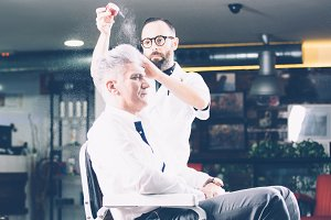 Barber powdering head of client