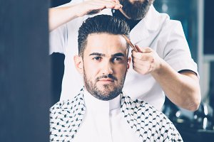 Barber combing stylish man