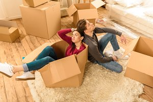 couple sitting on floor with boxes