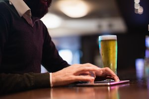 Man using digital tablet with glass of beer on counter