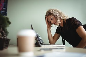Frustrated businesswoman working on laptop