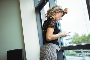 Upset businesswoman using mobile phone