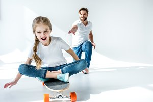 happy daughter sitting on skateboard