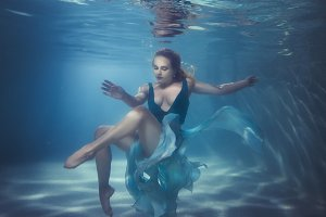 Woman dives underwater.