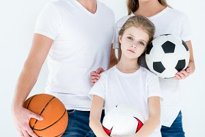 young family holding sports balls