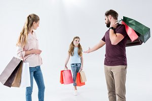 family standing with shopping bags