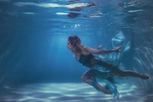Woman in a dress dives into the water.