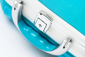 Closeup of blue suitcase handle on white