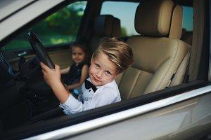 little boy driving car with girlfriend