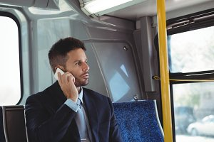 Businessman talking on the mobile phone while travelling
