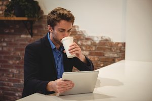 Businessman using digital tablet while having coffee