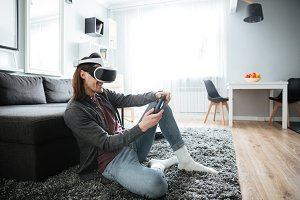 Happy man sitting play games with virtual reality glasses.