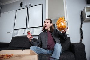 Screaming man sitting at home indoors eating crisps