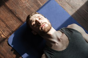 Concentrated young strong sportsman in gym lies on floor