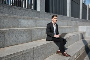Smiling young businessman sitting outdoors.