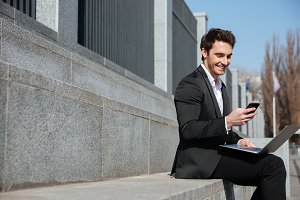 Smiling young businessman sitting outdoors chatting by phone.