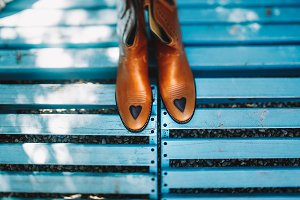 Brown boots on the blue bench