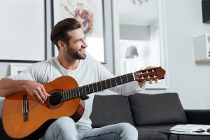 Happy man sitting on sofa playing on guitar