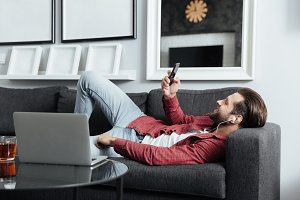 Happy young man lies on sofa listening music with earphones