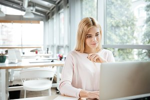 Concentrated lady sitting in office coworking while using laptop