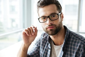 Handsome man wearing glasses sitting in office coworking