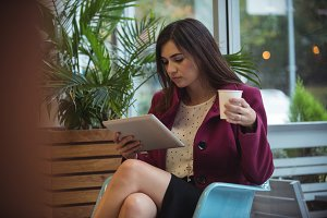 Businesswoman using digital tablet while having coffee in café