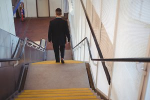 Businessman with a diary walking down stairs